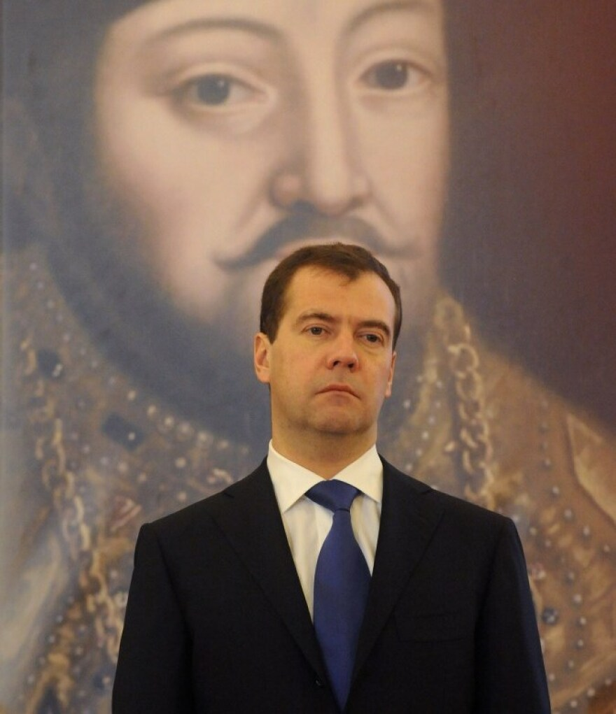 Russian President Dmitry Medvedev stands in front of a giant picture of Tsar Michael of Russia.