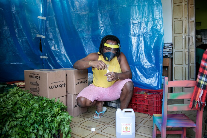 Dimas Reis, an activist who works to help residents of the favela Brasilandia, adds alcohol to a spray bottle so he can sanitize his hands while organizing food baskets donated by Pertim.