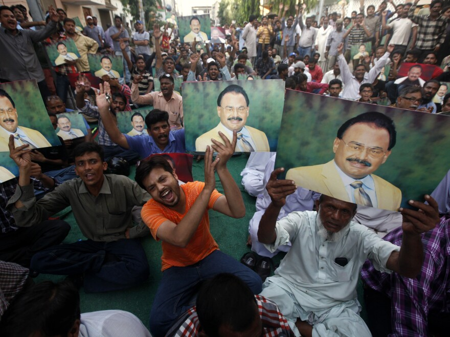 Supporters of Pakistan's Muttahida Quami Movement (MQM) political party hold posters of their leader Altaf Hussain, who was arrested in London, as they gather at the party's headquarters in Karachi on Tuesday.