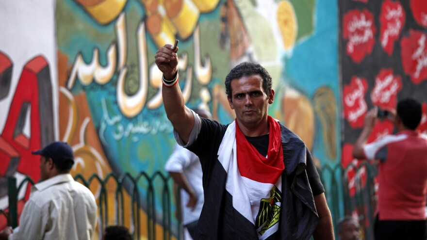 An Egyptian man waves a bullet casing in front of a mural that was painted on a recently whitewashed wall in Tahrir Square in Cairo.