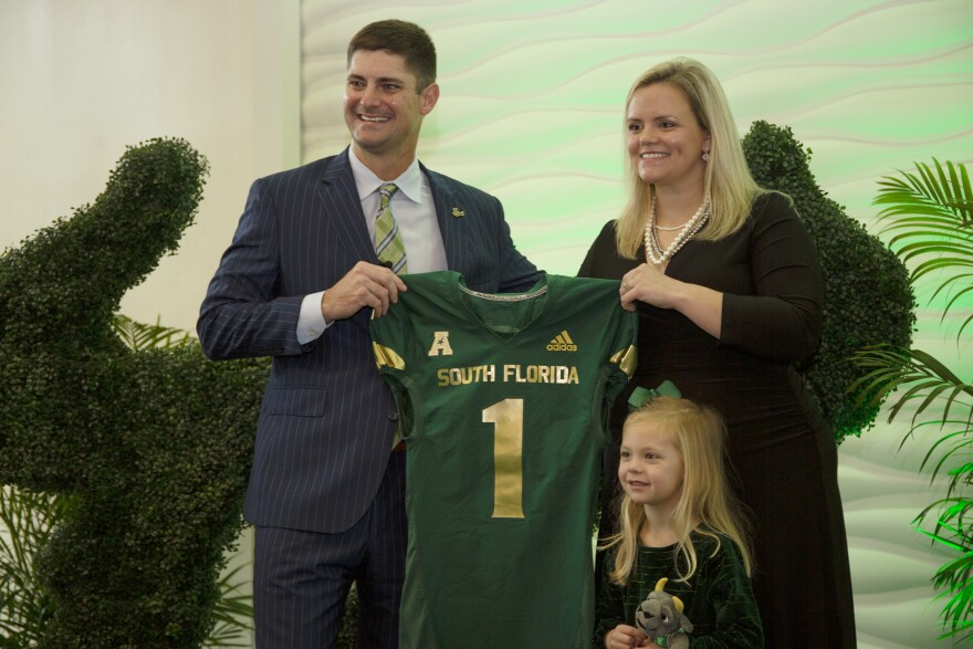 Man poses for picture with wife and daughter while holding USF football jersey.