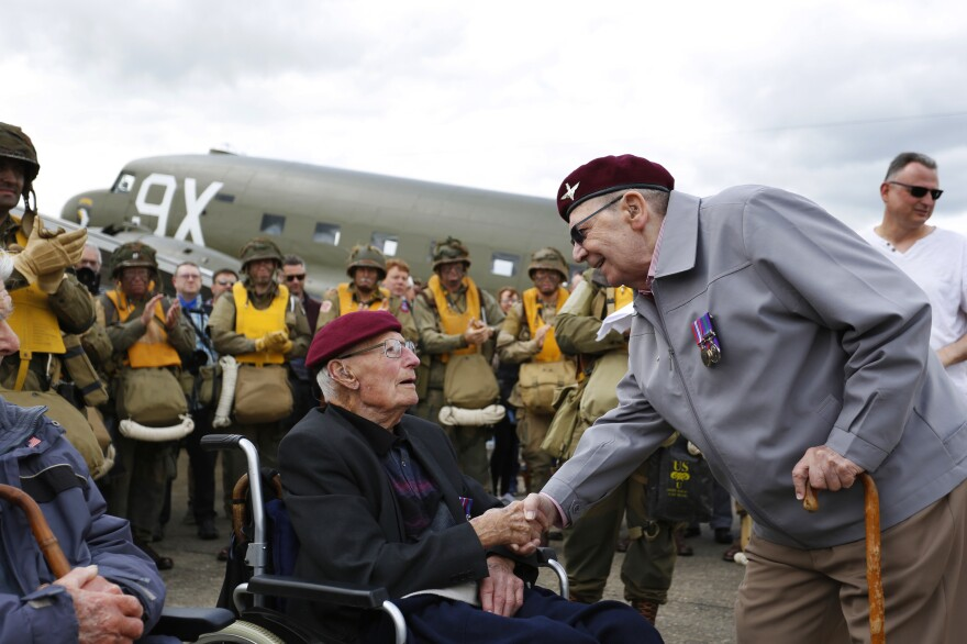 Two British World War II airborne veterans shake hands on the flight line at the Imperial War Museum Duxford.