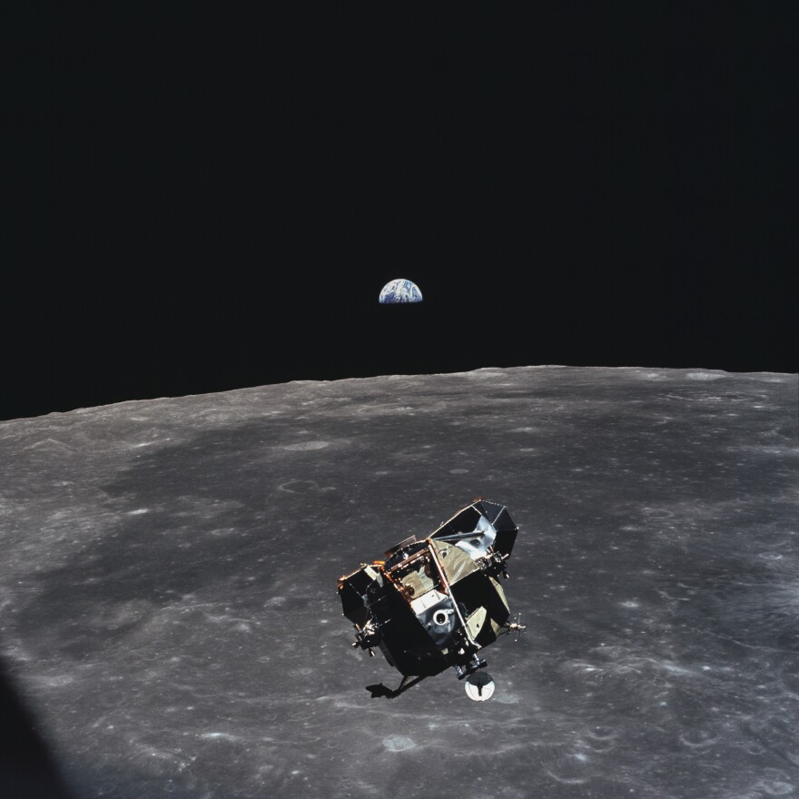 The Apollo 11 ascent stage, with astronauts Armstrong and Aldrin aboard, is photographed in lunar orbit. The lunar module was making its docking approach. The large, dark-colored area in the background is Smyth's Sea; Earth rises above the lunar horizon.
