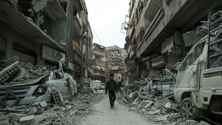 A Syrian child threads a path last week through the rubble of blasted buildings in the rebel-held town of Douma, in the enclave of eastern Ghouta outside Damascus.