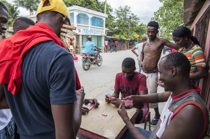 Men play dominoes by the street in Dosmond, Haiti.