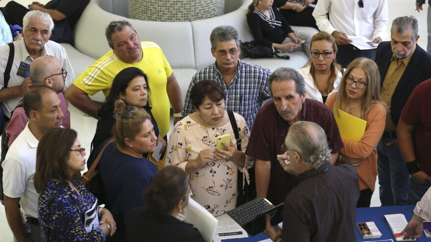 People inquire about temporary positions available for the 2020 census during a job fair in Miami in September 2019.