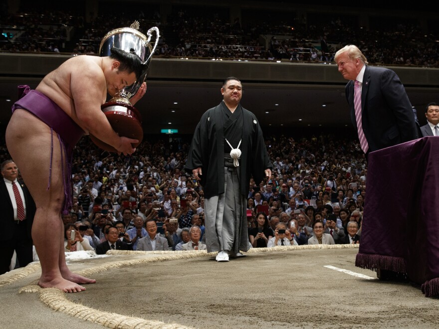 President Trump presents the President's Cup to the Tokyo Grand Sumo Tournament winner Asanoyama on Sunday.