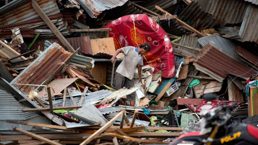 A man looks for his belongings amid the debris of his destroyed house in Palu after a strong earthquake and tsunami struck the area.