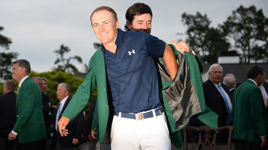Last year's champion, Bubba Watson, helps Jordan Spieth put on the iconic green jacket Sunday at the 79th Masters Golf Tournament at Augusta National Golf Club.
