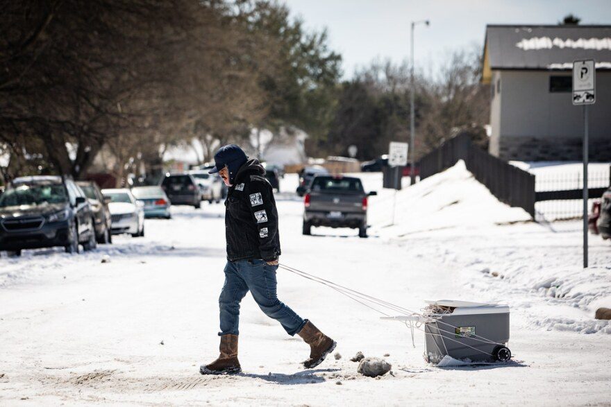 A person drags a cooler back from the HEB grocery store on South Congress Avenue on Tuesday.