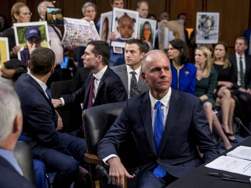 Boeing Company President and Chief Executive Officer Dennis Muilenburg (right foreground) with hearing attendees holding up photographs of those killed in the Ethiopian Airlines Flight 302 and Lion Air Flight 610 crashes.