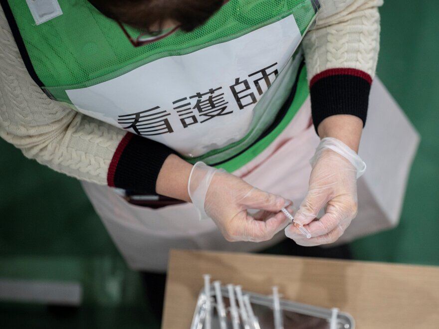 A nurse prepares syringes for a coronavirus vaccination drill in Kawasaki on January 27, 2021.