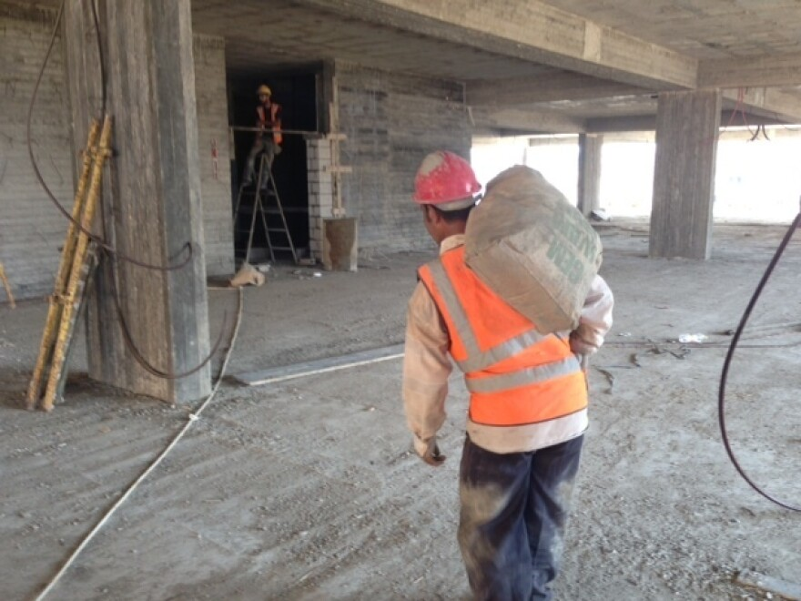 A worker carries a bag of cement for construction of a hospital in Gaza City in early October. This project, funded by Qatar, brought in cement from Egypt, with the excess given to the Hamas government. Since the end of this summer's war, the Qatari projects have been relying on the local black market for cement.