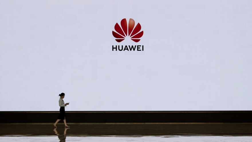 A member of Huawei's reception staff walks in the foyer of a building at the company's Bantian campus in April in Shenzhen, China.
