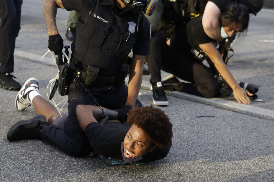 Demonstrators are detained by police during a protest in Atlanta. The protest started peacefully earlier in the day before demonstrators and police clashed.