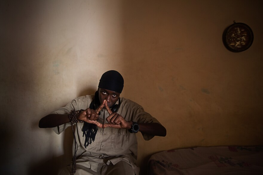 Zendang, a rapper from Mauritania, in his bedroom in Dakar. Below: Rappers perform on a small outdoor stage.