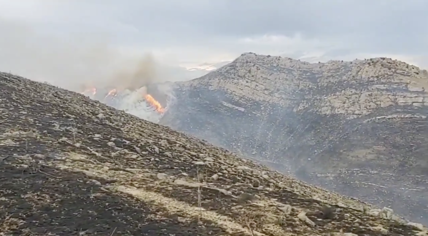 A wildfire burns up the left side of a distant ridge.