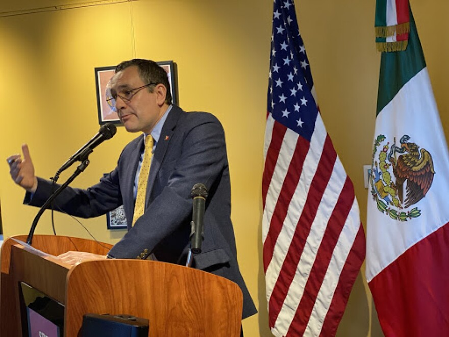 A man stands in a podium in front of the U.S. and Mexican flags.