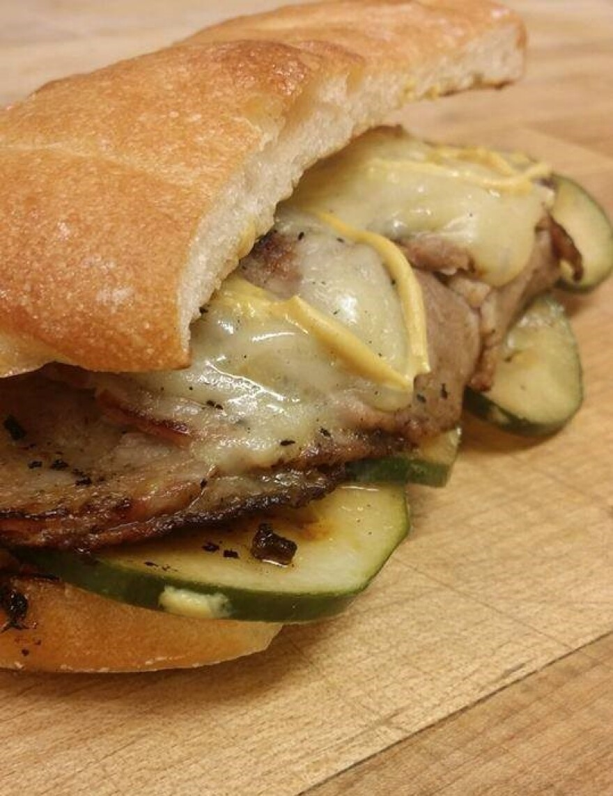 A sandwich with meat, cheese, pickles and mustard on a wooden surface.