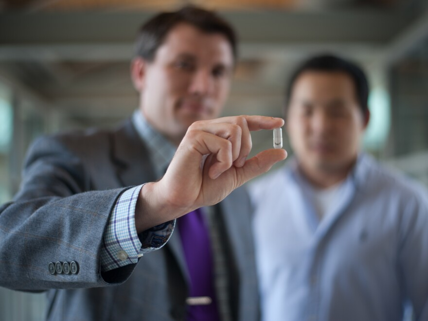 Chris Bettinger (left) holds the edible battery he designed with Young Jo Kim and other researchers at Carnegie Mellon University in Pittsburgh.