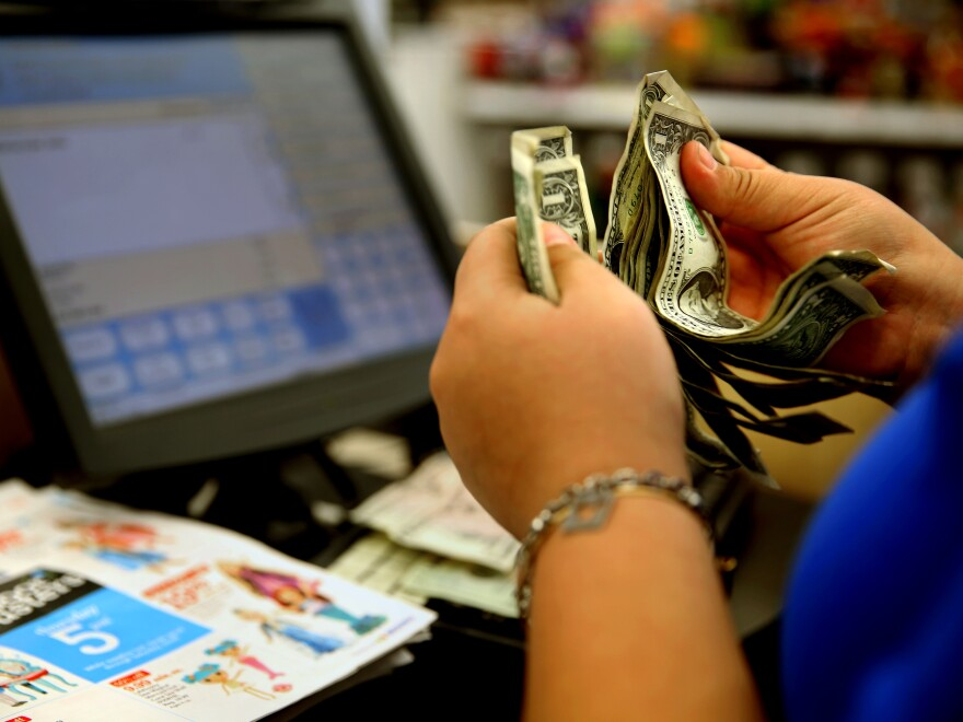 "A cashier counts money at a Toys ""R"" Us in Los Angeles last November. A pinch in earnings and hours disappointed those looking for a pickup in paychecks last month."