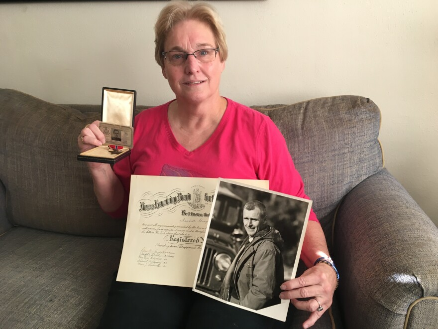 Laurie Staver Clinton holds her parents' World War II memorabilia.