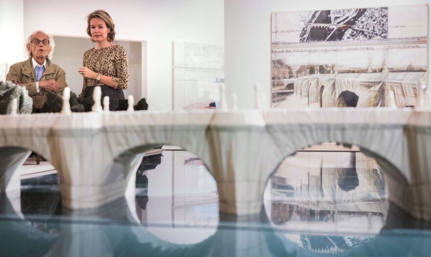 "Artist Christo talks to Queen Mathilde of Belgium by a model of the 1985 Paris project ""The Pont Neuf Wrapped"" during a visit to the exhibition ""Christo and Jeanne-Claude: Urban Projects"" at the ING Art Center in Brussels in 2017."