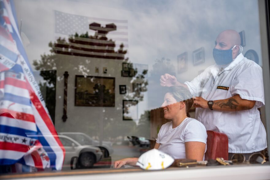 A barber cuts a woman's hair at a salon amid the coronavirus pandemic in Round Rock, Texas, on May 8, following a slow reopening of the Texas economy.