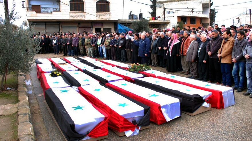 Syrians pray on Jan. 10 beside the coffins of people killed by a car bomb a day earlier in the central city of Hama. Syrian peace talks are planned next week in Geneva, Switzerland.