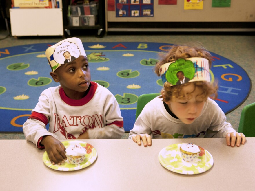 Jonah Hack (left) and Kieran Dockett-Gilbert wait for Barnhardt's permission to dig into their cupcakes. The treats were part of their Rev. Martin Luther King Jr. birthday celebration on Friday, which also included songs and stories.