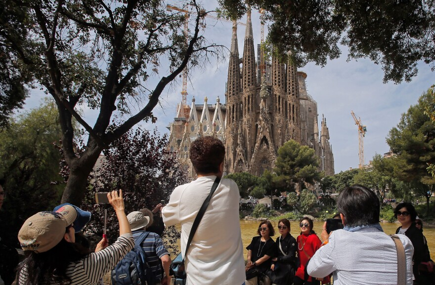 Tourists take pictures in front of Barcelona's Sagrada Familia church. The city of 1.6 million gets more than 30 million tourists a year.