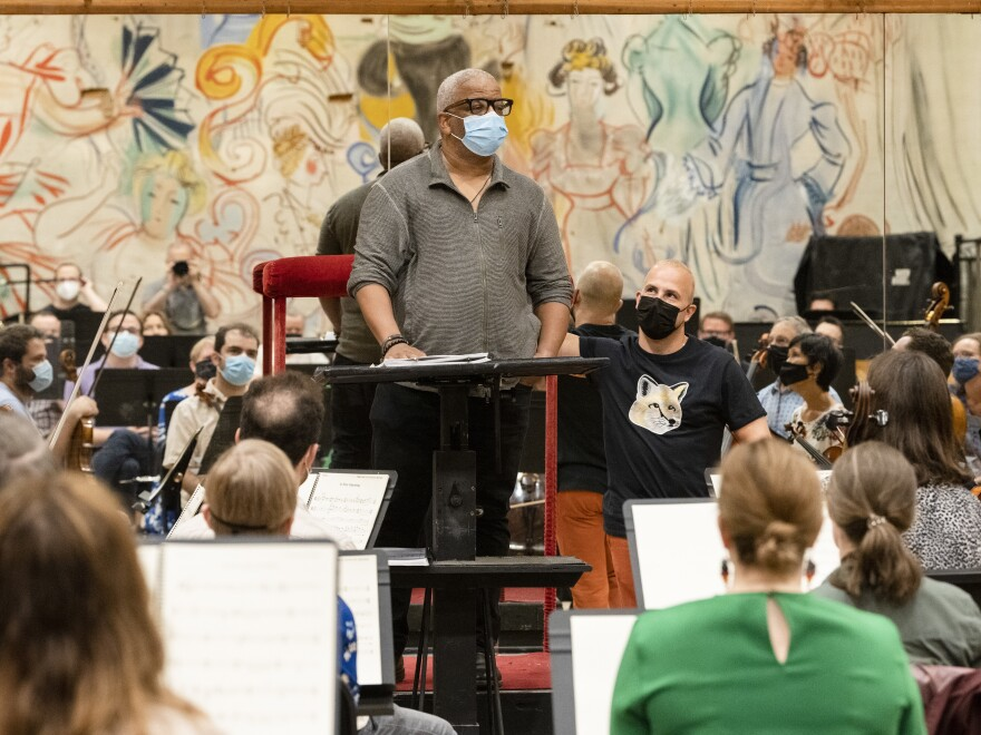 Terrence Blanchard (center) addresses Metropolitan Opera Orchestra members in rehearsal, with music director Yannick Nézet-Séguin looking on.