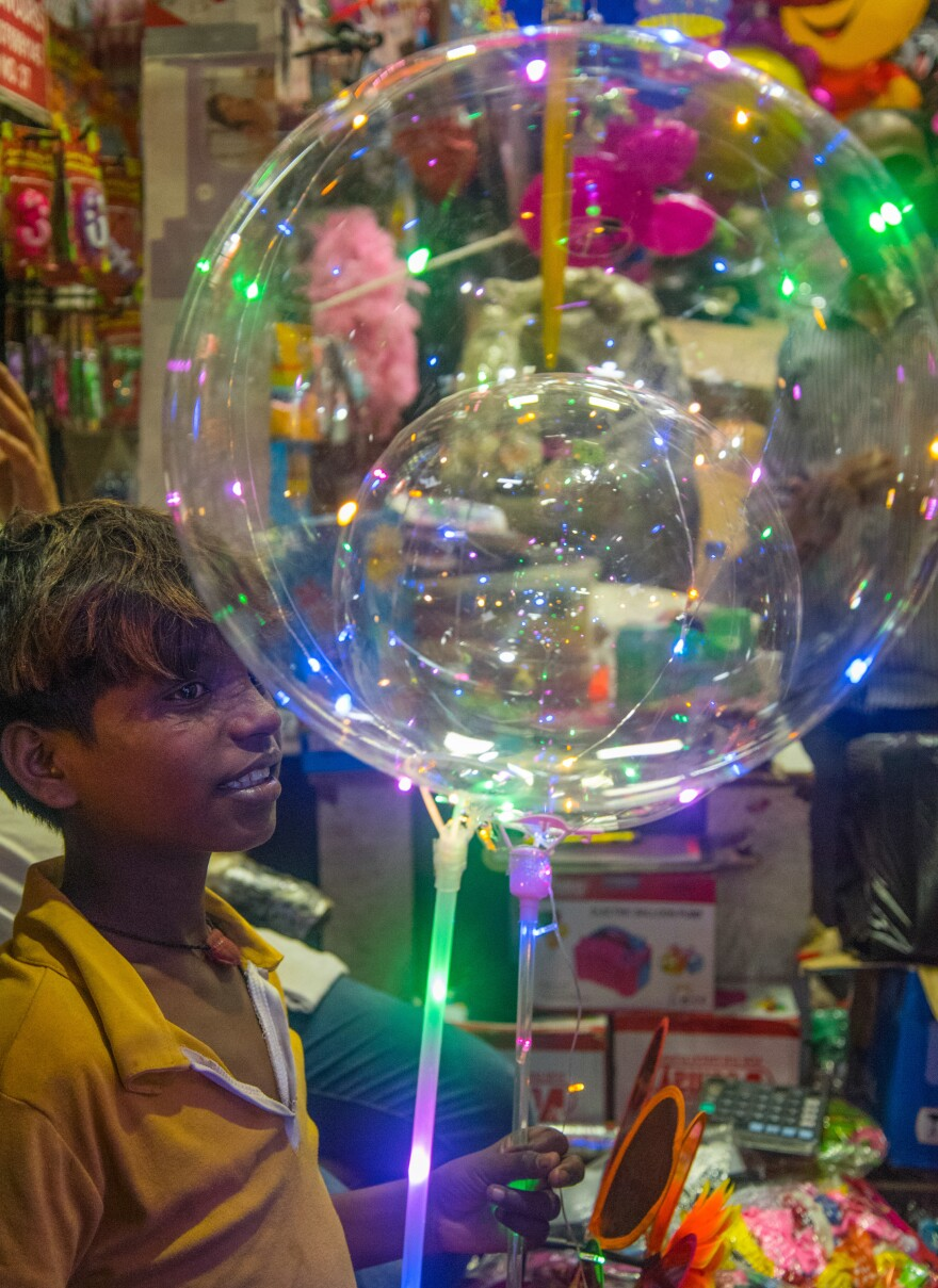 Jitender, 12, and his mother, Barkha, took a two-day train trip from her home state of Assam to New Delhi to buy 500 LED balloons to sell on the street.