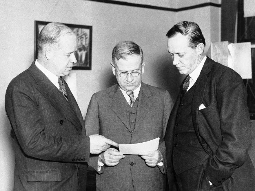 From left: Frank C. Walker, Harold L. Ickes and Harry L. Hopkins talk before making a radio address to explain the new works program on May 16, 1935.