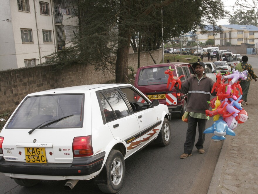 A vendor sells toys to drivers caught in Nairobi traffic. Drivers who get traffic reports by text message could avoid congested routes or consider taking back streets, many of which are underused.