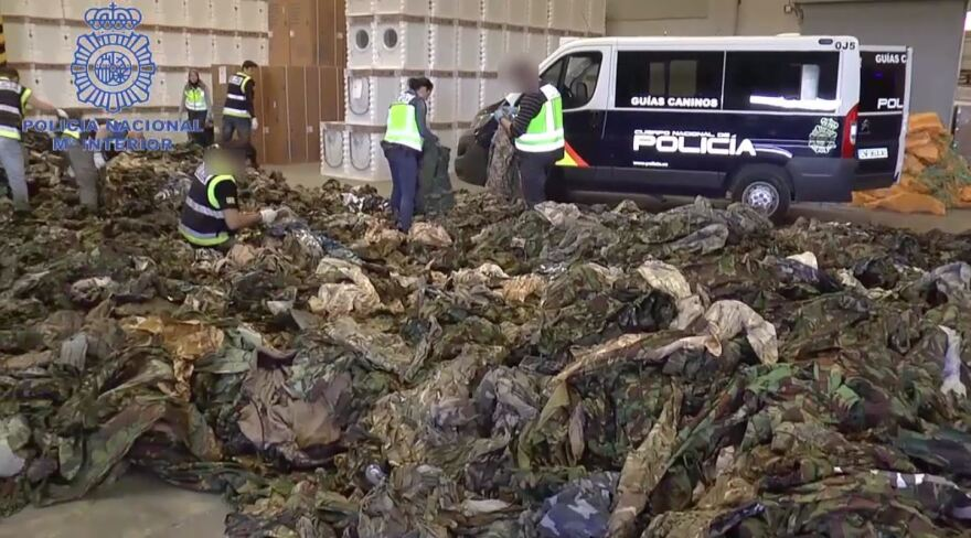 Police go through thousands of uniforms that were intercepted in three shipping containers at Spanish ports Thursday.