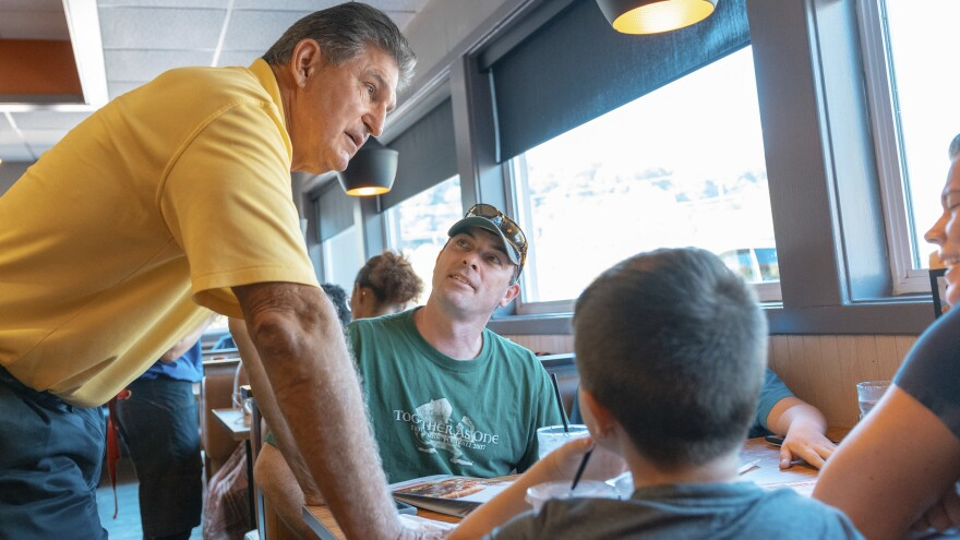 Democratic Sen. Joe Manchin (left) speaks to Jason and Loarie Butcher of Pinch W.Va., last month at an IHOP restaurant in Charleston, W.Va., about his recent vote in the Senate to confirm Supreme Court Justice Brett Kavanaugh.