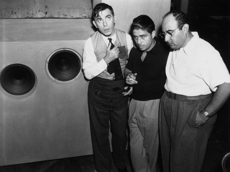 Alfred Newman stands between actor Eddie Cantor (left) and director Norman Taurog, listening to a playback on the set of <em>Strike Me Pink</em>, circa 1935.