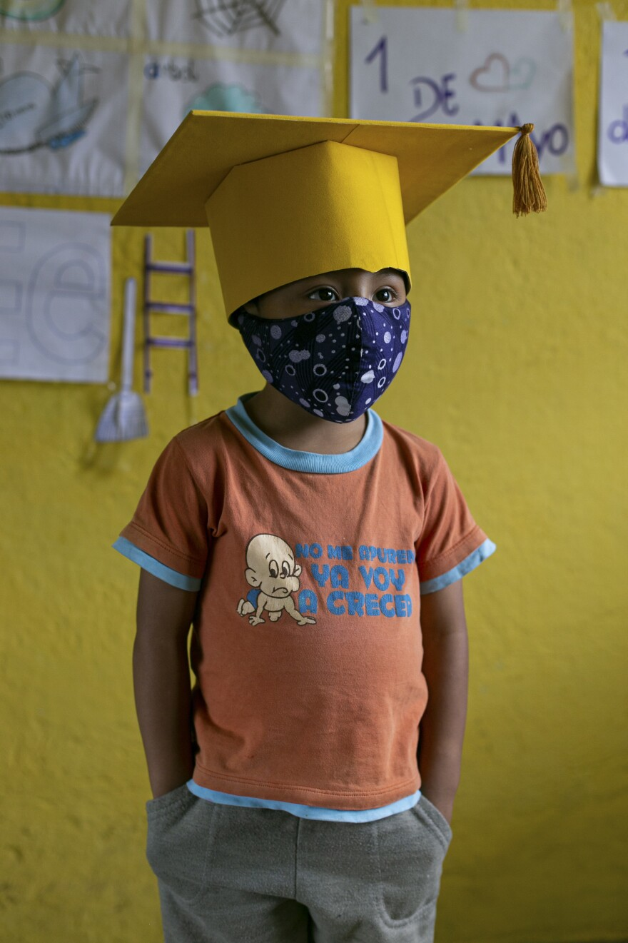Gael Pin, 4, wears a cap and mask for the closing ceremony of his school year. Because Gael's family doesn't have an internet connection, they plan to watch the ceremony at their neighbor's house. <em>June 18. Cotogchoa, Ecuador.</em>