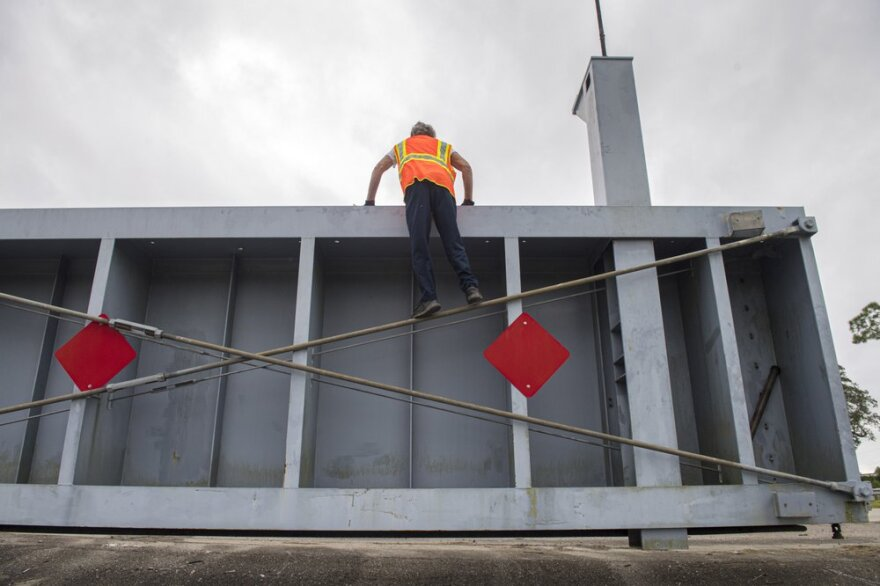 Workers move a levee gate