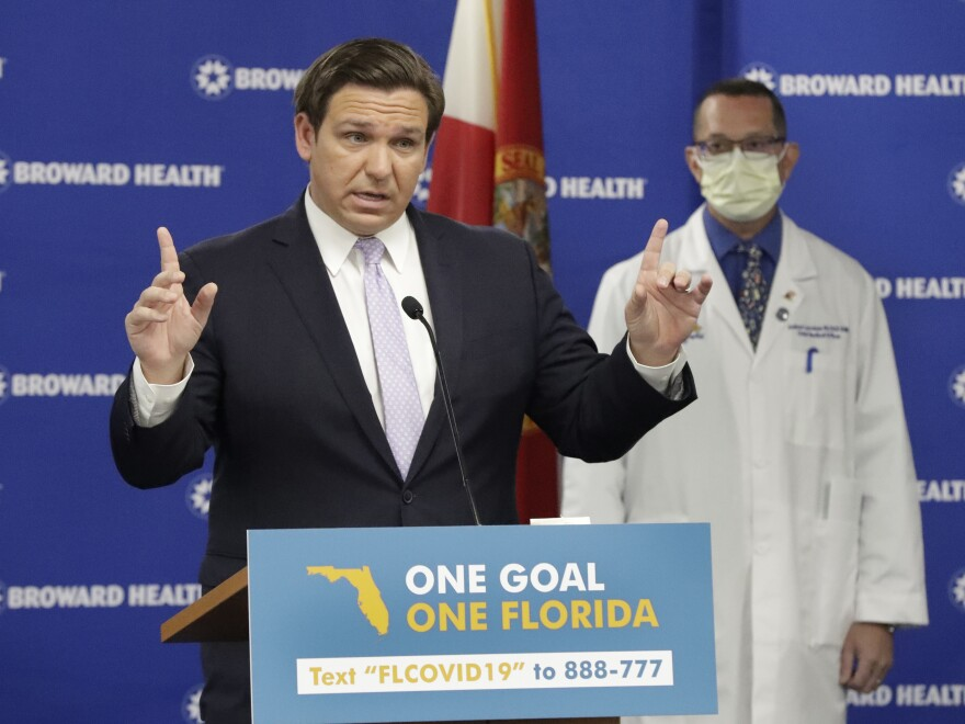Florida Gov. Ron DeSantis speaks during a news conference Monday along with Dr. Joshua Lenchus, chief medical officer of Broward Health Medical Center. DeSantis says he's exploring ways to open nursing homes for family member visits.