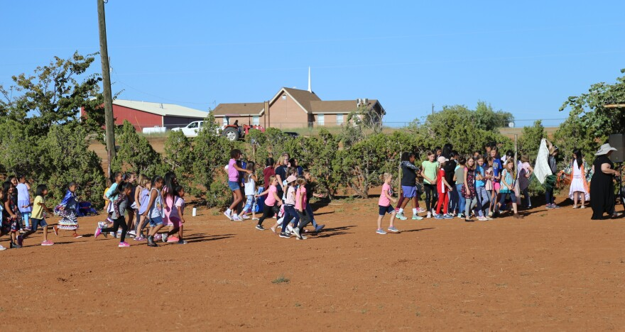 Photo of a large group of young girls running in a corral with red dirt.