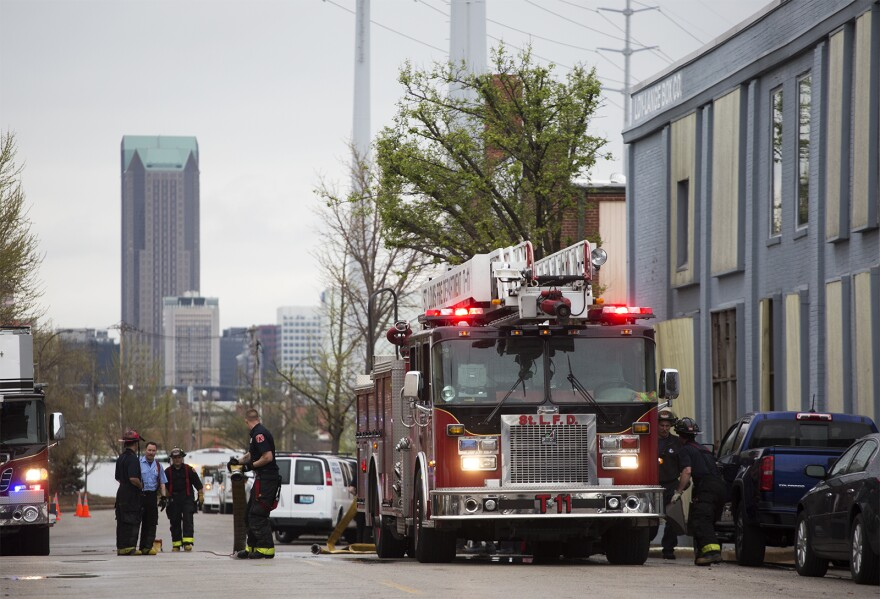 Firefighters work outside of the Loy-Lange Box Company building on South 3rd Street. (April 3, 2017)