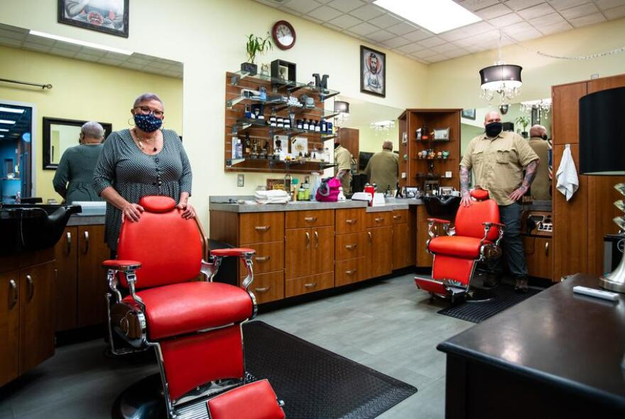 two barbers standing behind empty red barber chairs.