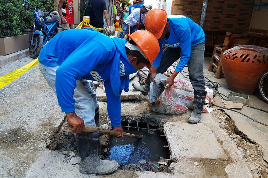 Municipal workers try to clear sewage from one of the alleys leading to White Beach before it overflows. The scene is repeated all over the island as residents try to cope with overbuilding and often illegal connections to the sewage system.