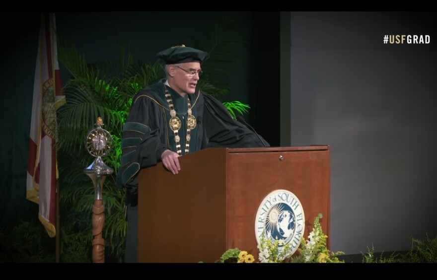 man in cap and gown speaks from podium