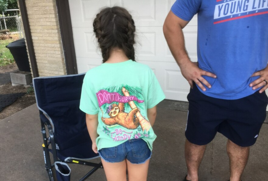 a child, from the back showing off her t-shirt showing a drawing of a sloth waving a banner that says Don't Hurry