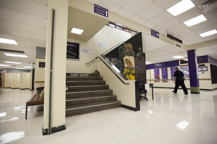 A police officer walks through the hall of LBJ High School in 2016.
