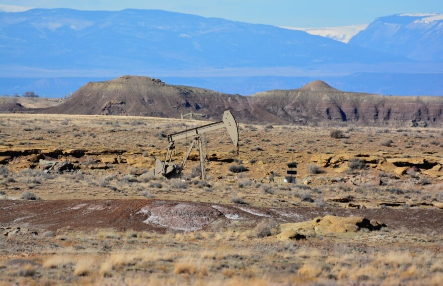 Photo of a pumpjack in a valley with mountains behind it.