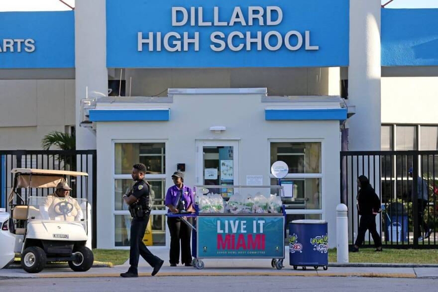 Dillard High School employees wait for students and parents to arrive to get packaged breakfasts in Fort Lauderdale on March 16. Broward County schools are closed because of the spread of COVID-19.